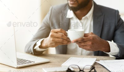 Pensive businessman drinking coffee at workplace, thinking about new project