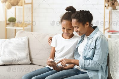 Two adorable sisters using smartphone on sofa at home