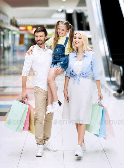 Cheerful Father Carrying Little Daughter On Family Shopping In Mall