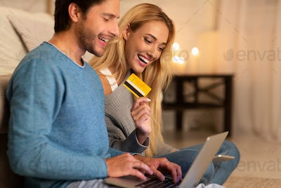 Man And Woman Shopping Holding Laptop And Credit Card Indoor