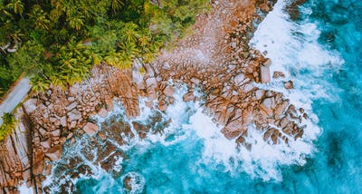 Aerial drone view of tropical coastline with turquoise ocean waves splashing against bizarre granite