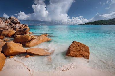 Grand anse, La Digue island, Seychelles. Sandy beach with orange granite boulders and azure ocean