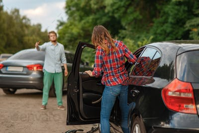 Male and female drivers after car accident on road