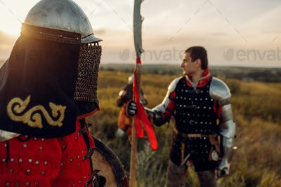 Medieval knights in armor and helmet at sunset