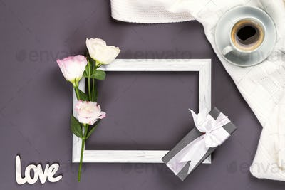 Having a cup of coffee , flowers eustoma and gift box on a frame on blanket on a dark background