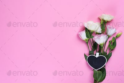 Bouquet blooming pink eustoma with a chalkboard on pink background, flat lay. Valentines day