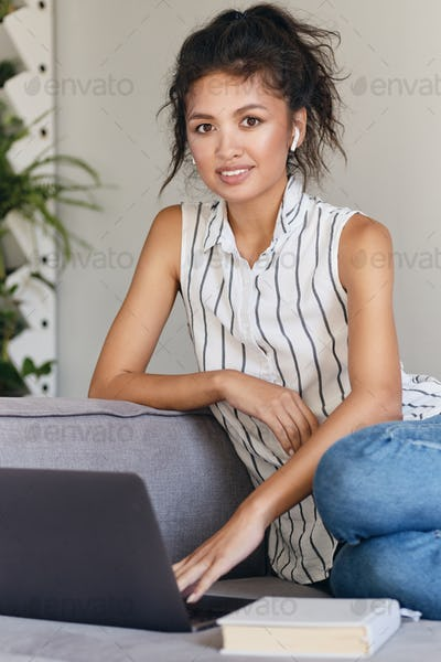 Pretty casual Asian girl happily looking in camera working on laptop at modern home