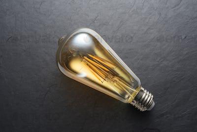 Transparent LED filament light bulb on black slate background.