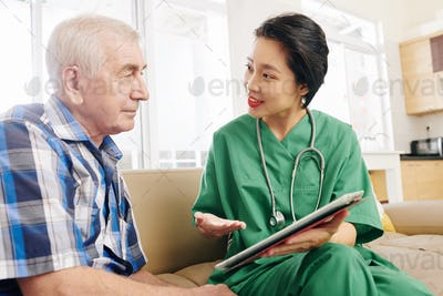 Hospital worker visiting senior patient at home