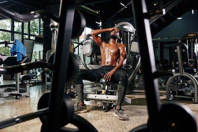 Tired shirtless sportsman resting in gym machine