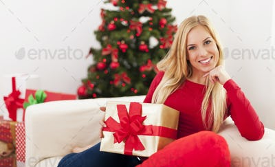 Beautiful blonde woman sitting in living room during the christmas time