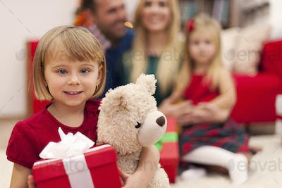 Portrait of little girl with her teddy bear and family in christmas time
