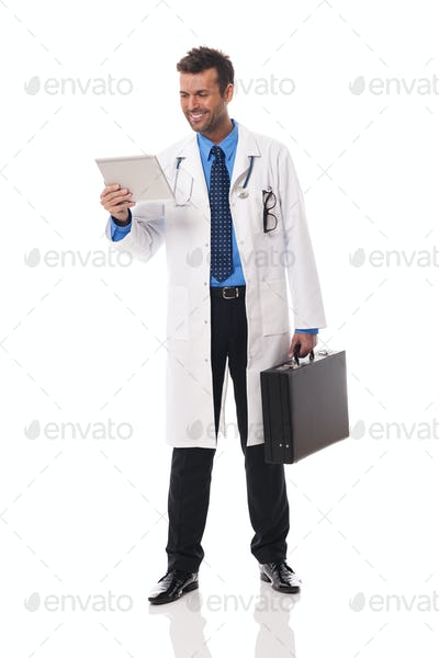 Smiling doctor checking something on digital tablet