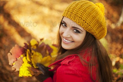 Beautiful woman holding leaves in sunny autumn day