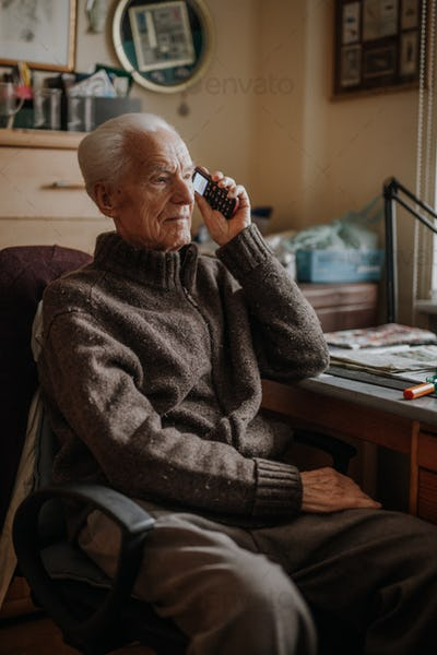 Old elder senior man talking on mobile phone