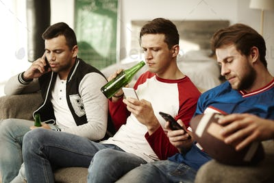 Men using mobile phone during commercial break