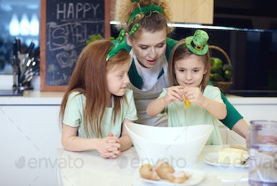 Cheerful siblings with mother baking cookie