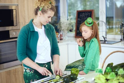 Woman teach child how to cut vegetable