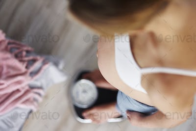 High angle view of pregnant woman standing on scale