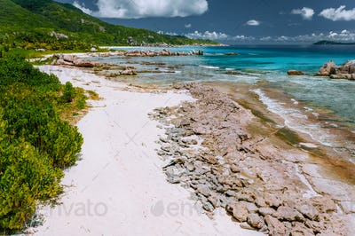 Old coral reef in the white sand beach on secluded beach of grand anse, La Digue, Seychelles. Aerial