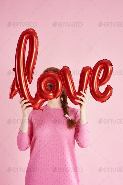 Young woman covering her face with balloon at studio shot