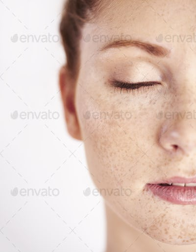Half of woman's face with freckle