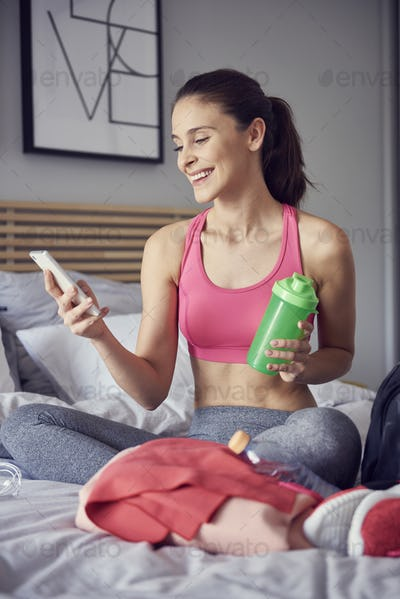 Cheerful athlete using a mobile phone at bedroom