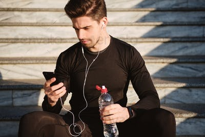 Attractive sporty man in earphones thoughtfully using cellphone on stairs after workout outdoor