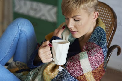 Woman wrapped in a blanket drinking tea in winter day