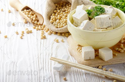 Soy Bean curd tofu in clay bowl and in hemp sack on white wooden