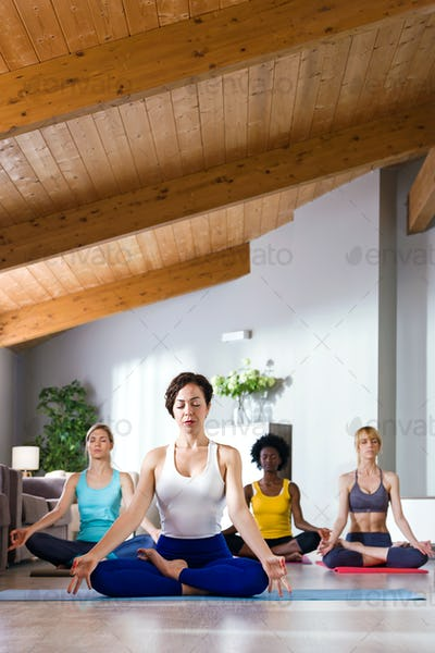 Group of pretty young sporty women practicing yoga at home