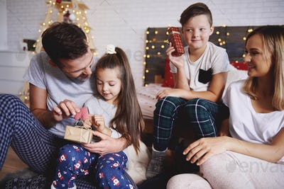 Happy family opening christmas presents in bed
