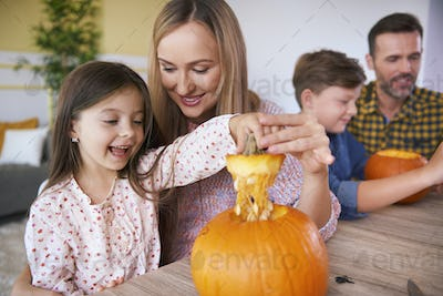 Children carving pumpkins with parents for Halloween