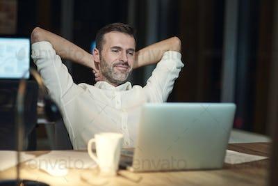Satisfied man resting in his office