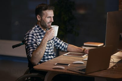 Side view of disabled businessman working late
