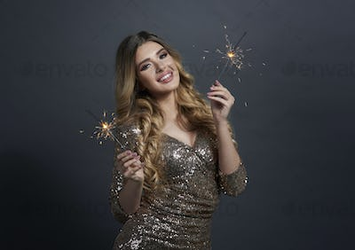 Portrait of happy woman with burning sparklers at studio shot