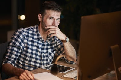 Focused businessman using a computer at night