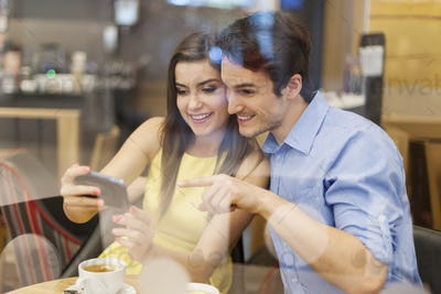 Beautiful couple in cafe with mobile phone