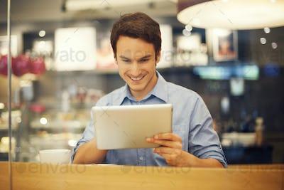 Smiling man using digital tablet in cafe