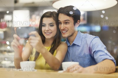 Happy couple checking something on mobile phone in cafe
