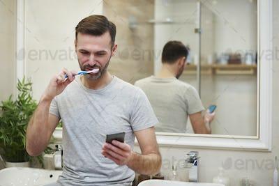 Man brushing his teeth and using mobile phone in bathroom