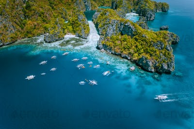 Aerial view of amazing Mililoc Island. Tourist boats near big Lagoon. El Nido, Palawan, Philippines