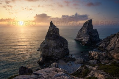 Hidden Praia Da Ursa - Ursa Beach, Sintra, Portugal. Two huge rocks rasing in evening golden sunset