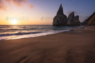 Ursa Beach, Sintra, Portugal. Sand beach with rocks silhouette in evening soft golden sunset light