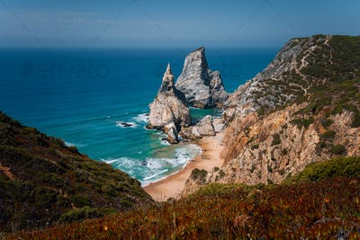 View of a hidden Praia Da Ursa Beach in sunset evening light near Cabo Da Roca on Atlantic coast