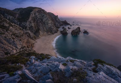 Sunset over a hidden surreal Praia Da Ursa Beach near Cabo Da Roca on Atlantic coast, Portugal