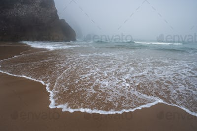Praia da Adraga beach - White ocean waves and silhouette of costal rocks in morning fog. Sintra
