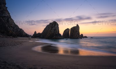 Epic Ursa Beach with rock silhouette and reflection against golden sunset light. Cabo da Roca