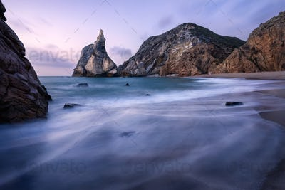 Epic Ursa Beach, Sintra, Portugal. Beach with waves and jugged rock peak in evening soft sunset