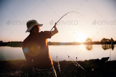 Young man fishing on lake at sunset enjoying hobby